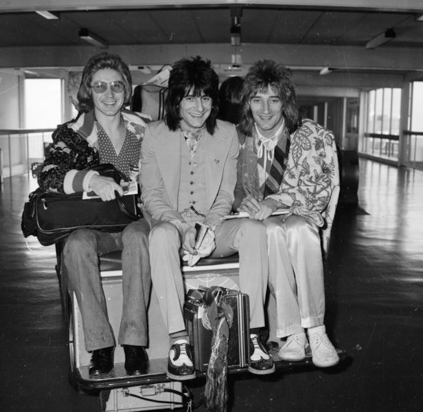 24th January 1974:  Members of The Faces on a luggage cart at London Airport (from left) Kenny Jones, Ron Wood and Rod Stewart.  (Photo by Dennis Stone/Express/Getty Images)