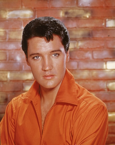 Portrait of American rock and roll singer Elvis Presley, dressed in an orange open-neck shirt and in front of a brick wall, mid 1960s. (Photo by Hulton Archive/Getty Images)